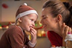 Mutter und Baby, die Weihnachtssnäcke in der Küche essen stockbilder