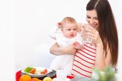 Mutter und Baby, die zu Hause essen Glückliches lächelndes Familien-Portrait stockbild