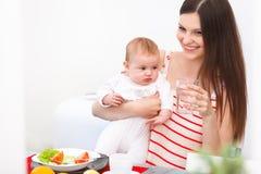 Mutter und Baby, die zu Hause essen Glückliches lächelndes Familien-Portrait stockfotos