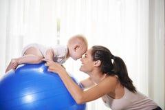 Mutter und Baby, die zu Hause trainieren lizenzfreie stockfotografie