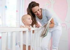 Mutter und Baby, die zusammen lesen lizenzfreies stockbild