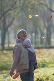 Mutter und Baby in einem Riemen freuen sich fallenden Herbstlaub stockfotos