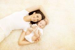 Mutter und Baby, glückliches Familien-Porträt, Mutter mit Kind auf Teppich stockfotos