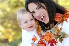 Mutter und Baby mit Blättern - Fall-Thema Stockfotos