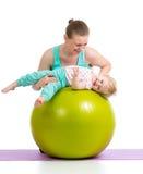 Mutter und Baby mit gymnastischem Ball Stockbild