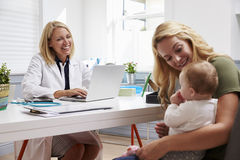 Mutter-und Baby-Sitzung mit Ärztin In Office lizenzfreies stockfoto