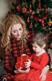 Mutter und Baby unter Weihnachtsbaum mit Geschenkbox lizenzfreie stockfotos