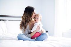 Mutter- und Babykind auf einem weißen Bett Stockfotos