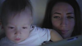 Mutter- und Babysohn, der mit der digitalen Tablette sitzt auf der Couch in zu Hause glätten spielt stock footage