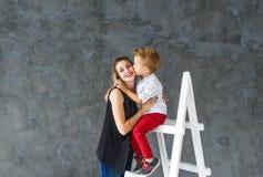 Mutter und blonder Sohn auf einem Bockleiter Lizenzfreie Stockbilder