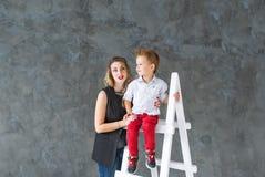 Mutter und blonder Sohn auf einem Bockleiter Stockbilder