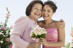 Mutter und Braut mit Blumenstrauß draußen (Porträt) lizenzfreies stockbild