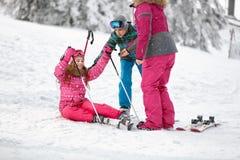 Mutter und Bruder lernt Mädchen, um vom Schnee mit Skis aufzustehen Lizenzfreies Stockfoto