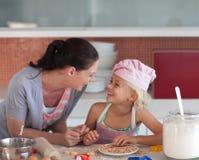 Mutter und Daugther, die in der Küche kochen lizenzfreie stockbilder