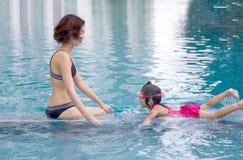 Mutter und daugther lieben, auf Swimmingpool zusammen zu schwimmen lizenzfreie stockfotografie