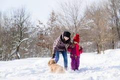 Mutter und daugther spielen mit einem Hund im Schneewald stockbild
