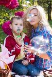 Mutter- und des Sohnsdurchbrennenseifenluftblasen Stockbilder
