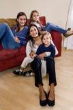 Mutter und drei Kinder, die zu Hause zusammen sitzen Lizenzfreie Stockfotos