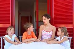 Mutter und drei Kinder sitzen auf Veranda Stockfotografie