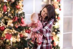Mutter und ein kleiner Junge verzieren den Weihnachtsbaum für das neue Jahr Neues Jahr ` s Dekor, neues Jahr ` s Märchen Stockfoto
