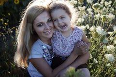 Mutter und eine Tochter in den Sonnenblumen Stockfotos