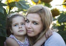 Mutter und eine Tochter in den Sonnenblumen Lizenzfreies Stockbild
