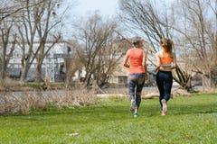 Mutter- und Erwachsentochter, die für Sport entlang dem Fluss läuft Stockfotografie