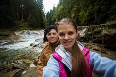 Mutter- und Erwachsentochter, die im Wald nahe dem Fluss sitzt und selfie nimmt Stockfotos