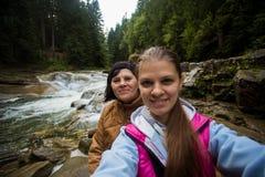 Mutter- und Erwachsentochter, die im Wald nahe dem Fluss sitzt und selfie nimmt Lizenzfreie Stockfotografie