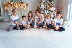 Mutter und fünf Kinder, die zu Hause Wunderkerze nahe Weihnachtsbaum spielen stockfotografie