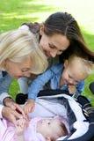 Mutter und Großmutter, die am Baby lächeln Lizenzfreie Stockfotografie