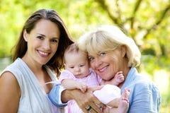 Mutter und Großmutter, die draußen mit Baby lächeln Lizenzfreies Stockbild