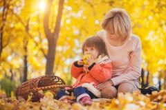Mutter und ihr Baby haben Spaß im Herbstpark stockfotos