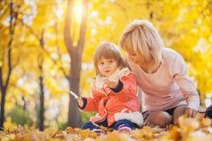 Mutter und ihr Baby haben Spaß im Herbstpark stockbild