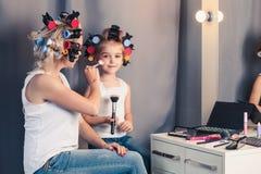 Mutter und ihr Kindermädchen tun Ihr Make-up und haben Spaß Stockbild