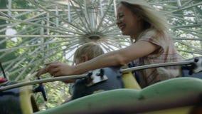 Mutter und ihr kleines Baby fahren auf Gleiskettenfahrzeug im Vergnügungspark 4k stock footage