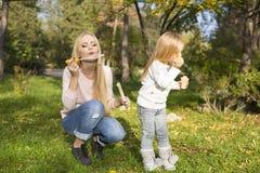 Mutter und ihr Kleinkind mit Seifenblasen Stockfoto