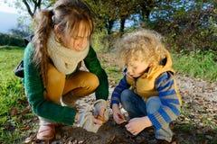 Mutter und ihr Sohn, die mit Herbstlaub spielen Lizenzfreie Stockfotografie