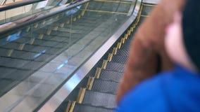 Mutter und ihr Sohn gehen die Rolltreppe hinunter Sie sind in der Winterkleidung, kamen ins Einkaufszentrum stock video footage