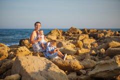 Mutter und ihr Sohn haben Spaß am Seestrand bei dem Sonnenuntergang Stockbilder