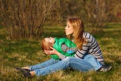 Mutter und ihr Sohn sind, spielend sitzend und auf dem Rasen Lizenzfreies Stockfoto