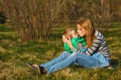 Mutter und ihr Sohn sind, umarmend sitzend und auf dem Rasen Lizenzfreie Stockfotos