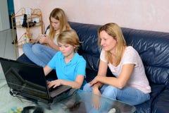 Mutter und ihre Kinder, die Computer verwenden Lizenzfreie Stockfotografie