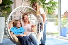 Mutter und ihre Kinder, die einen Smartphone verwenden Lizenzfreie Stockfotografie
