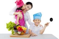 Mutter und ihre Kinder machen einen Salat stockbilder