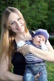 Mutter und ihre kleine des Sohns Sitzung draußen Lizenzfreie Stockfotografie