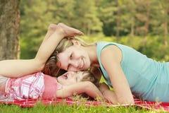 Mutter und ihre kleine Tochter auf Gras lizenzfreie stockfotos