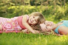 Mutter und ihre kleine Tochter auf Gras stockbilder