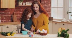 Mutter und ihre kleine Tochter bereiten sich für Ostern vor Glückliche Familie, die Malerei Ostereier in der gemütlichen Küche zu lizenzfreie stockbilder