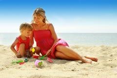 Mutter und ihre kleine Tochter, die auf dem Strand spielen lizenzfreies stockbild